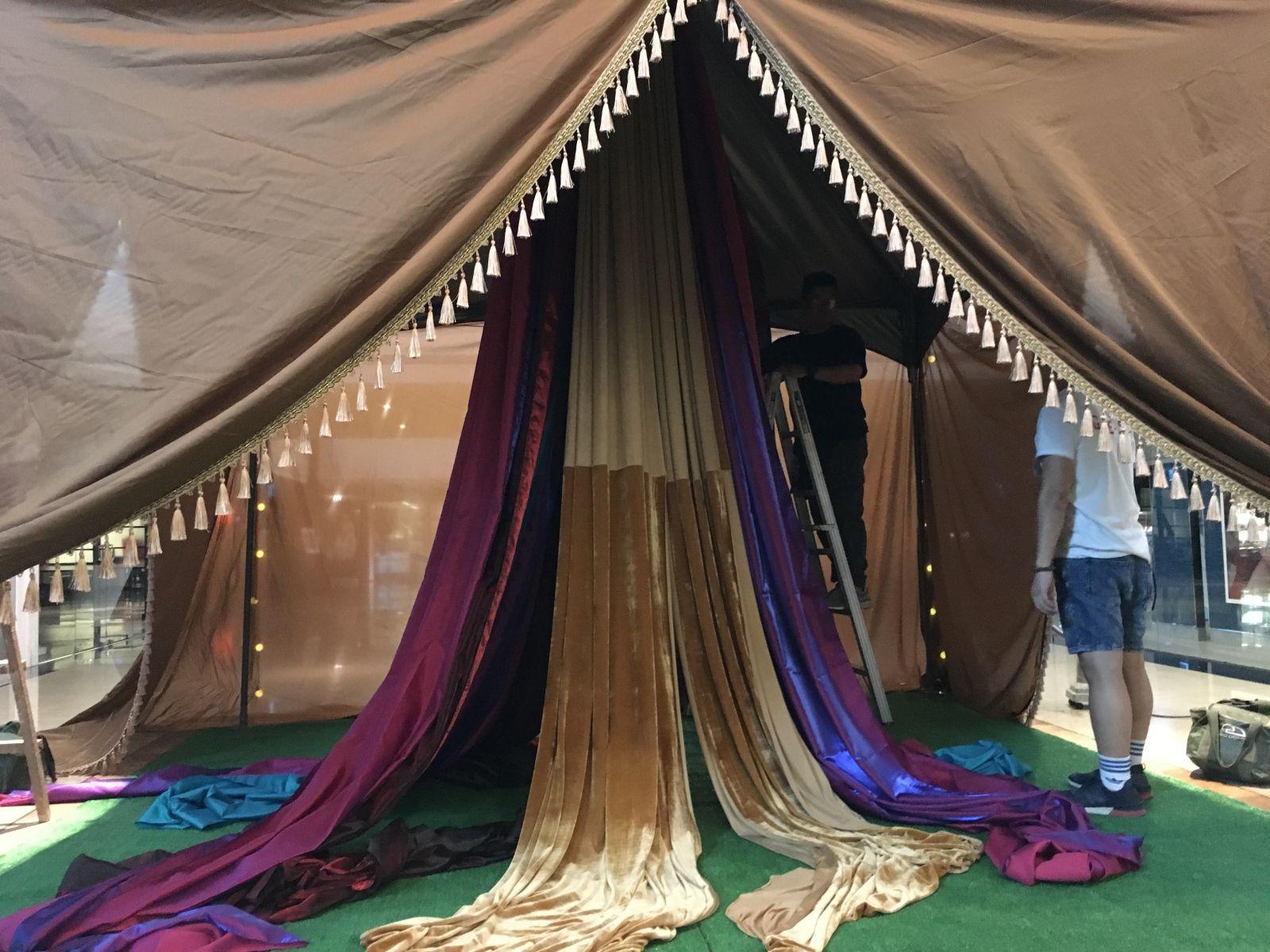 一起用力地將布幔串掛上帳篷內側頂端